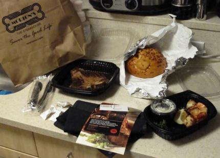 A steak, prawns, potatoes, bread, napkin and silverware.